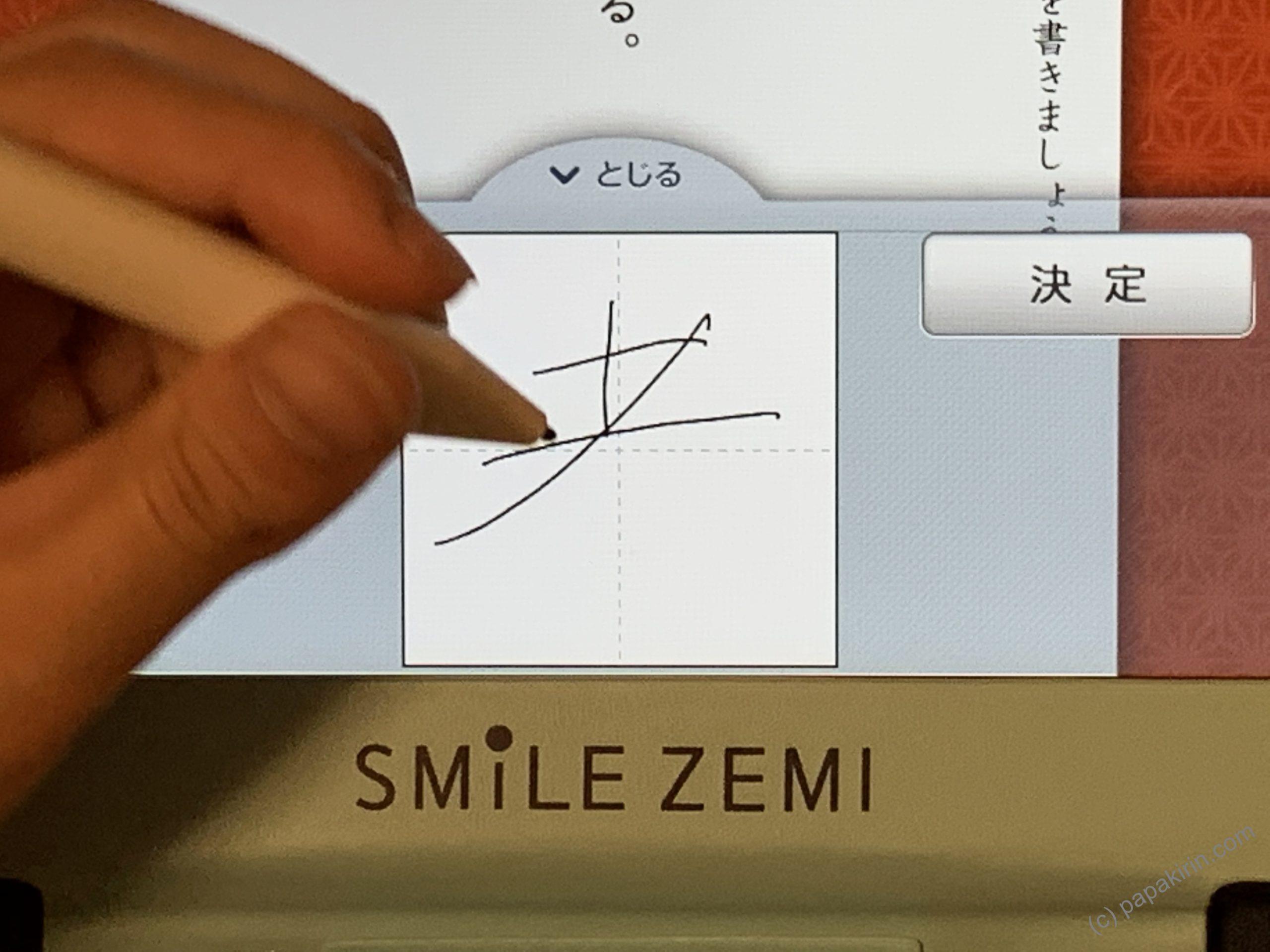 スマイルゼミの専用タブレットに手をついて漢字を書く写真